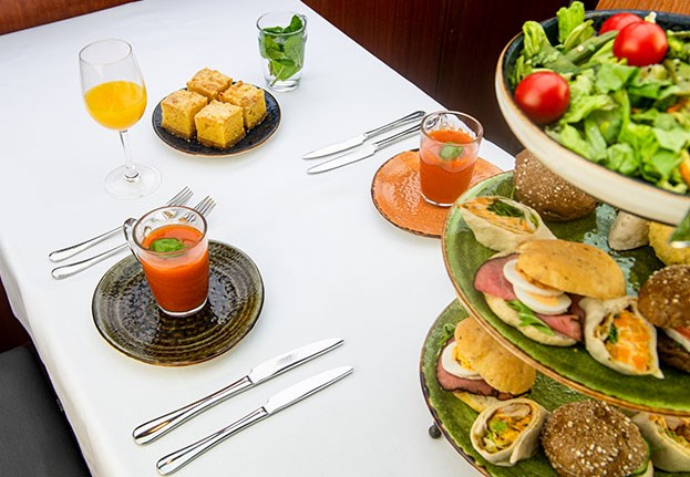 Table full with different sandwiches, a salad, tomato soup and orange juice