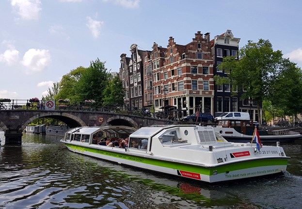 Hop On Hop Off white-green boat cruising through the prettiest Amsterdam canals