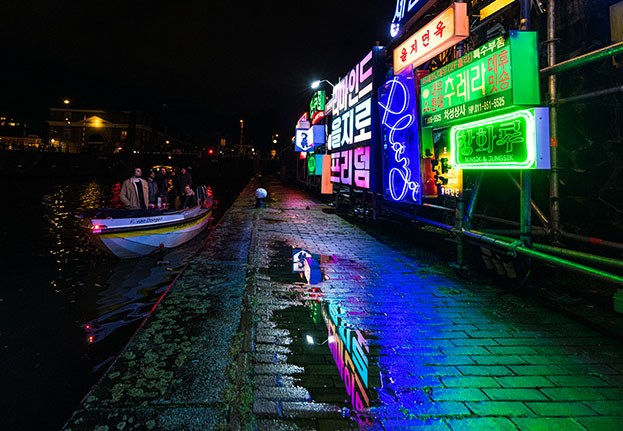 Open boat with a colorful artwork of Korean flickering advertisements